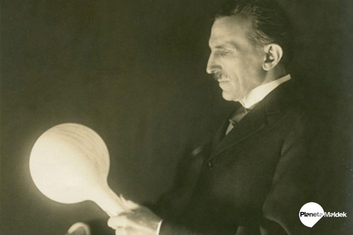 Nikola Tesla junto a la bombilla que desarrolló